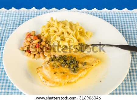 Boneless and Skinless chicken breast in lemon-butter and white wine sauce topped with capers.  Served with pasta and cannellini bean salad.  Overhead view. - stock photo
