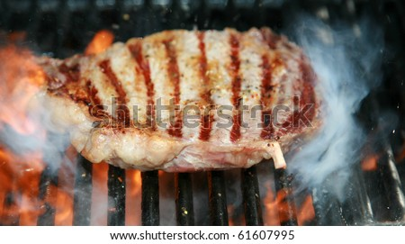 Boneless Rib-eye steak cooking on a barbecue with flames and smoke