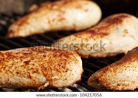 Boneless skinless chicken breasts on a charcoal grill - stock photo