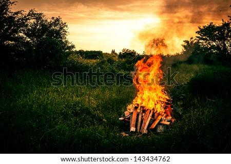 Bonfire at a camp in natural surroundings - stock photo