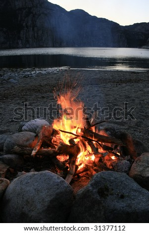 Bonfire at night by a Norwegian Fjord - stock photo