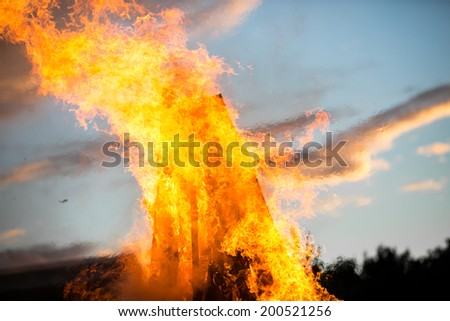 Bonfire on a summer night with beautiful sunset sky - stock photo