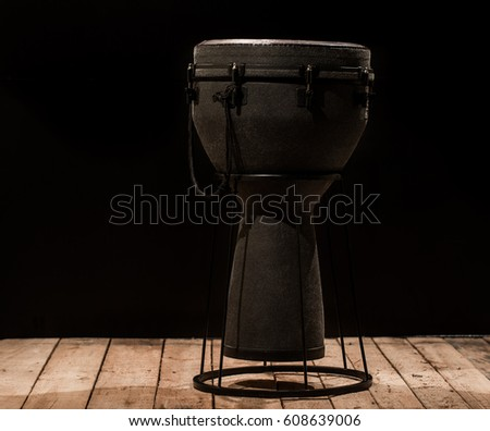 bongo drum on a black background placed on a wooden floor ,the concept of musical instruments
