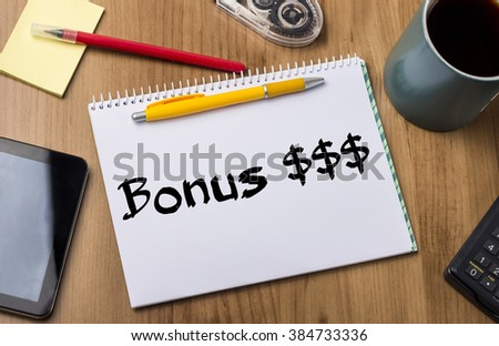 Bonus $$$ - Note Pad With Text On Wooden Table - with office  tools - stock photo