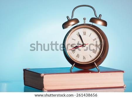 Book and alarm clock - stock photo