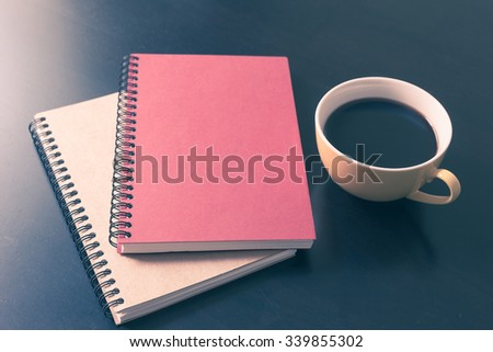 Book and coffee cup on black wooden table background - stock photo