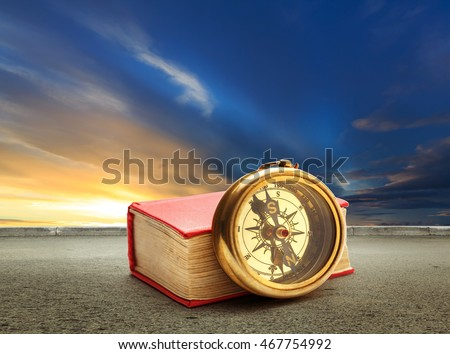 Book and compass at sunset sky with road background