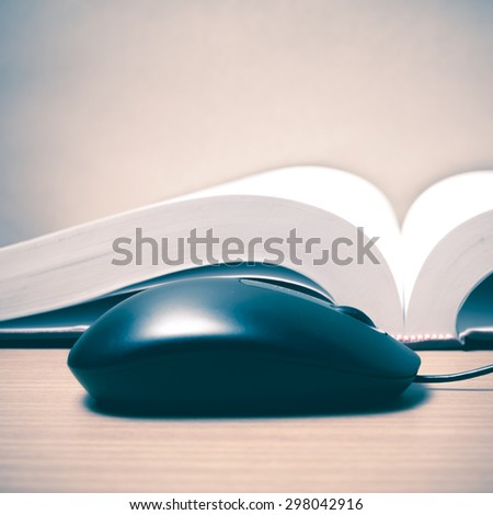 book and computer mouse on wood background vintage style