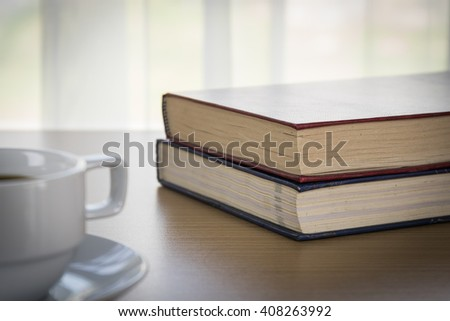 Book and Cup of coffee on wood table and red book - stock photo