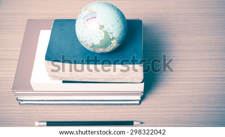book and earth ball with black pencil on wood background vintage style - stock photo