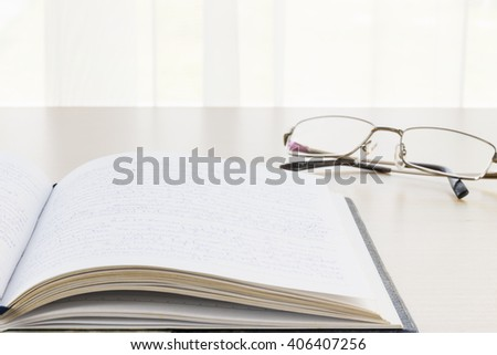 Book and eyeglasses with on the desk, 