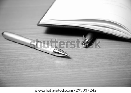 book and pen on wood background black and white color tone style