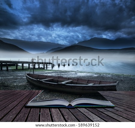 Book concept Stormy sky landscape over misty mountain lake with old boat on lake shore - stock photo