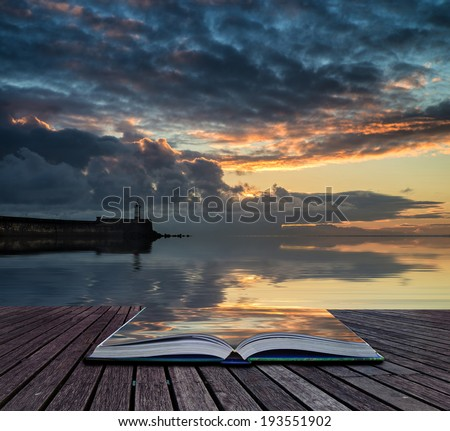 Book concept Stunning sunrise over ocean with lighthouse and harbor wall - stock photo