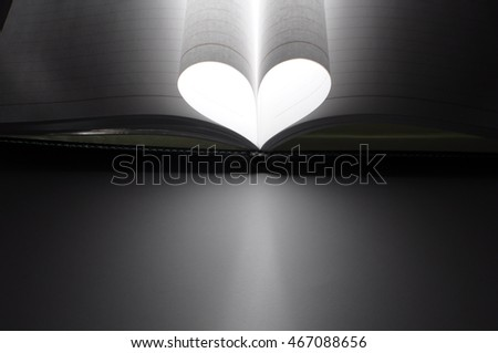 Book folded into a heart shape and a light shone through.