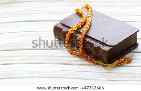 book in a vintage leather bound, and amber beads  - stock photo
