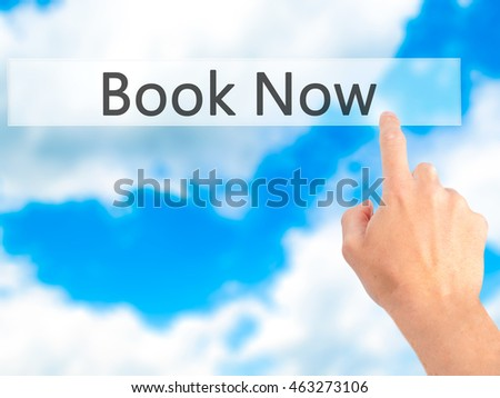 Book Now - Hand pressing a button on blurred background concept . Business, technology, internet concept. Stock Photo