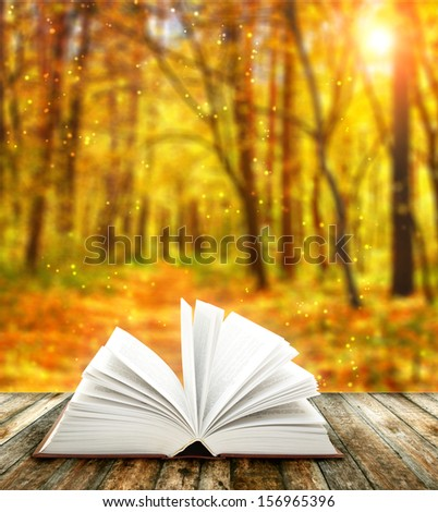 Book of nature on autumn forest background - stock photo