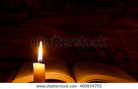 book on a wooden table with candlelight