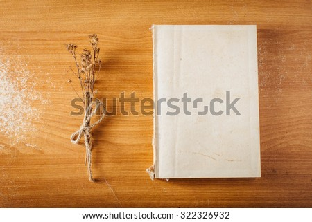 book on wooden table with dry grass