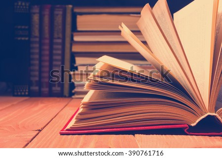 Book opened in library on wooden shelf. Education background with copy space for text. Toned photo - stock photo