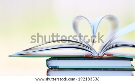 Book page in heart shape with green garden background - stock photo