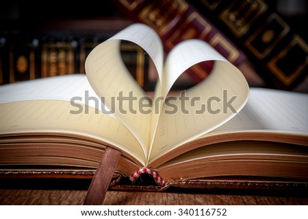 Book page in heart shape with library background.