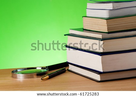 book, pen and magnifying glass on table - stock photo
