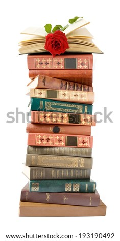 Book pile with rose on top isolated on white background.Teacher's Day concept - stock photo