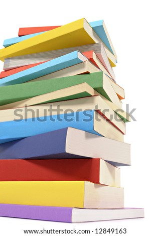 Book stack : low angle view of an untidy pile of colorful paperback books isolated on white background.  Vertical format.