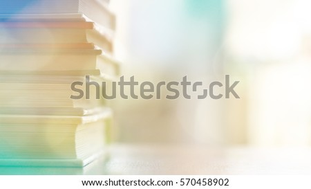 Book stack on wood desk and blurred bookshelf in the library room, education background, back to school concept