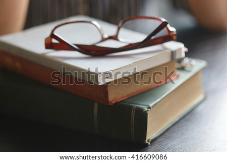 book stacked and eyeglasses, soft focus,layout writing pen on paper page,hardworking for achievement business target concept, knowledge concept with eyeglasses on vintage book.  - stock photo