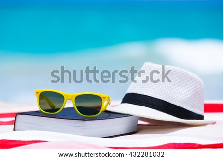 Book sunglasses and hat on the beach. - stock photo