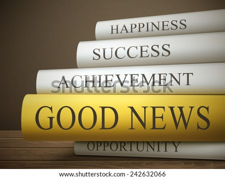 book title of good news isolated on a wooden table over dark background - stock photo