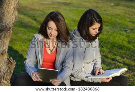 Book vs Tablet - two beautiful young women reading outside using a tablet and a book - stock photo