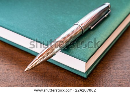 Book with a pen on the table - stock photo