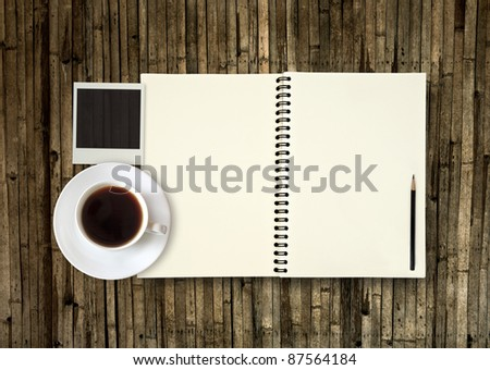 Book with coffee on bamboo plate