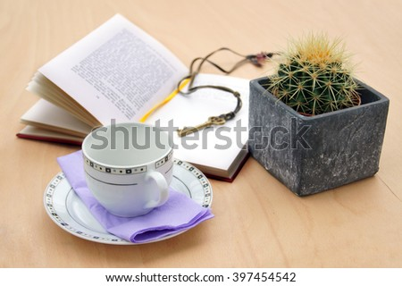 Book with key, cactus and a cup                 - stock photo