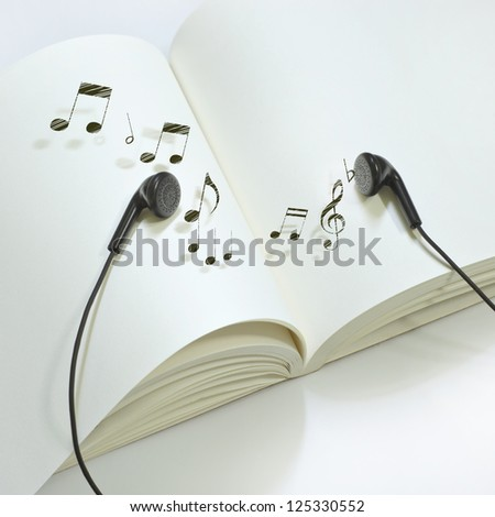 Book with melody of earphone - stock photo