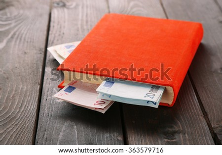 Book with nested euro banknotes on wooden table. Stash of money - stock photo