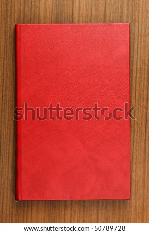 Book with red leather cover on wooden tabletop - stock photo