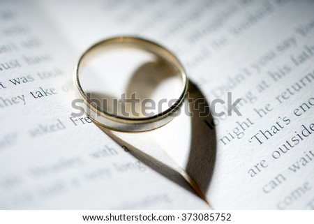 Book with Ring and heart shadow / Ring and book - stock photo