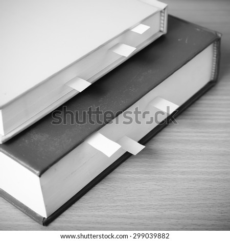 book with sticky note on wood background black and white color tone style