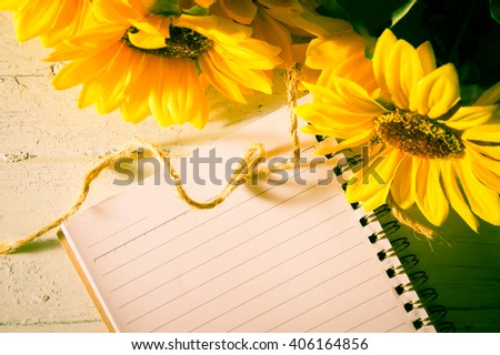 Book with sun flowers on table,vintage filtered.