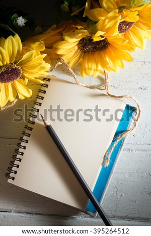 Book with sun flowers on wood table