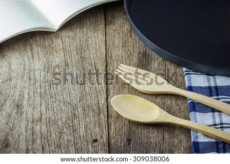 Book with wooden spoon and wooden fork on wooden background