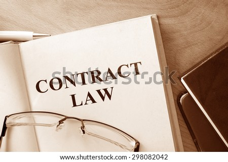 Book with words contract law and glasses.