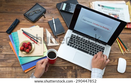 Booking flight tickets on-line concept. Man working on computer booking air flight tickets screen searching best offer from London to Beijing wooden desk stationery books pen pencil color on table - stock photo