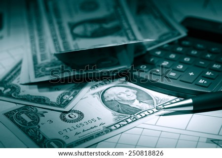 Bookkeeping concept. Closeup of dollar bank notes near calculator and pen on dark background - stock photo