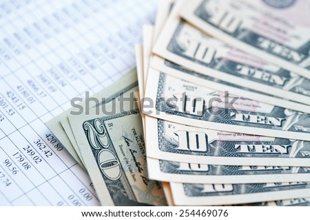 Bookkeeping concept. Closeup of dollar bank notes on paper list with digits - stock photo